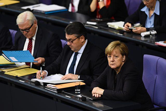 Kanzlerin Angela Merkel (R) mit dem deutschen Vizekanzler , Wirtschafts- und Energieminister Sigmar Gabriel (C) und dem deutschen Außenminister Frank-Walter Steinmeier (L) während einer Sitzung des Deutschen Bundestages  in Berlin, 25. November 2015. Foto: TOBIAS SCHWARZ / AFP / Getty Images