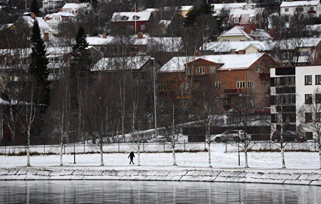 Eine Frau geht neben dem Storsjon See in Östersund, Schweden am 30. November 2012. Foto: JONATHAN NACKSTRAND / AFP / Getty Images