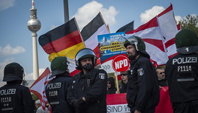 Aktivisten der NPD hinter einer Polizeilinie zu Beginn eine Demonstration in Berlin 2014. Foto: ODD ANDERSEN / AFP / Getty Images