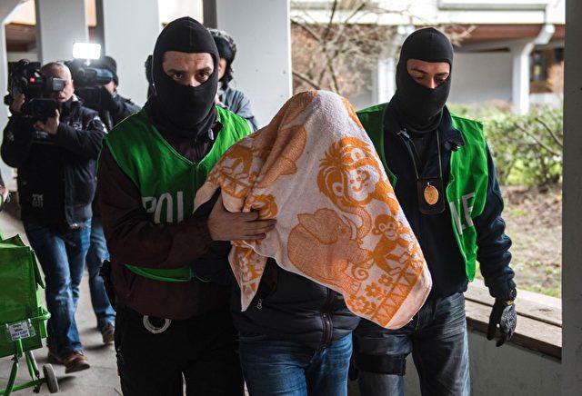Polizeibeamte begleiten einen Mann, der in einer Wohnung bei einer Razzia am 4. Februar verhaftet wurde. Zwei Algerier mit möglichen Verbindungen zum islamischen Staat wurden während einer Operation in Berlin am 4. Februar 2016 festgenommen. Foto: ODD ANDERSEN / AFP / Getty Images