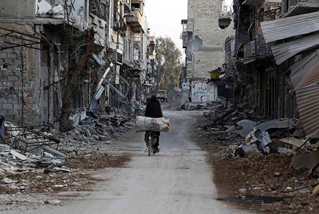 Ein Mann fährt mit seinem Fahrrad durch eine vom Krieg beschädigte Straße in Damaskus am 24. Februar 2016. / AFP / Foto: Abdulmonem Eassa / AFP / Getty Images