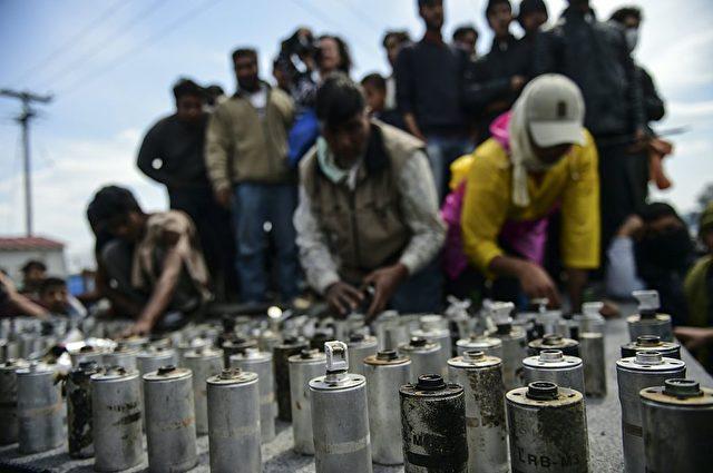 Migranten zeigen die leeren Tränengas-Kanister der mazedonischen Polizei, die am Sonntag auf sie geworfen wurden.