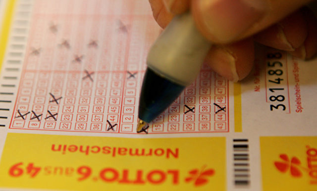Ein Mann beim Ausfüllen eines Lottoscheins. Foto: Martin Rose / Getty Images