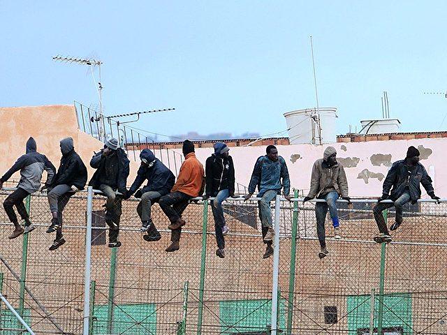 Migranten auf einem Zaun zwischen Marokko un der spanischen Enklave Melila im Februar 2015. Foto: ANGELA RIOS/AFP/Getty Images