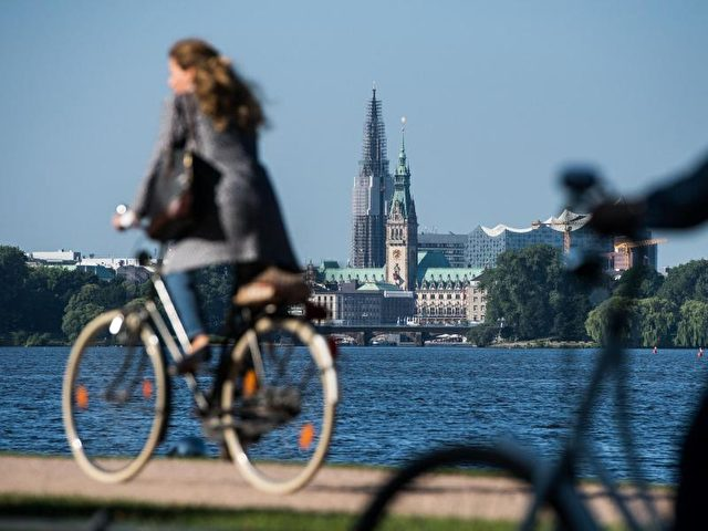 Fahrradfahrer an der Außenalster in Hamburg. Nach diversen Regentagen läßt sich zumWochenstart die Sonne sehen. Foto: Lukas Schulze/dpa