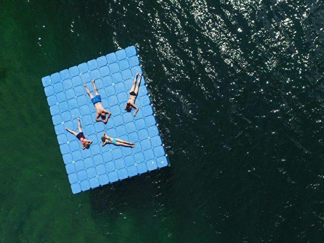 Sonnenbad auf einer Plattform im Wasser des Helenesees nahe Frankfurt/Oder. Foto: Patrick Pleul/dpa