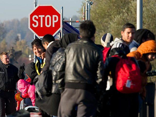 Flüchtlinge warten in Simbach auf der Innbrücke auf ihren Grenzübertritt. Foto: Angelika Warmuth/Archiv/dpa