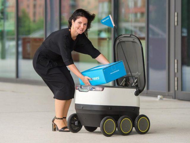 Daniela Kirchner von dem Paketlieferanten Hermes belädt einen von der Firma Starships Technologies entwickelter Roboter. Foto: Daniel Bockwoldt/dpa
