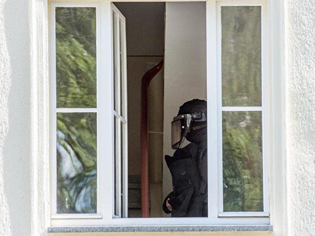 Ein Beamter des Spezialeinsatzkommandos im Haus des Verdächtigen. Foto: Patrick Pleul/dpa