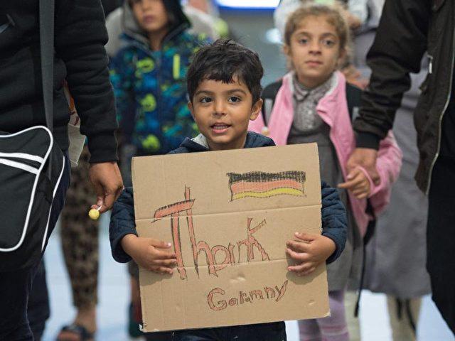 Zu früh bedankt?Ein kleiner Junge aus Syrien hält bei seiner Ankunft in Deutschland ein Schild mit der Aufschrift «Thank Germany» in den Händen. Foto: Sebastian Kahnert/Archiv/dpa