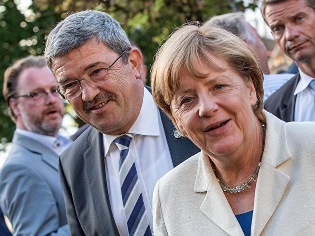 Bundeskanzlerin Merkel und der Innenminister von Mecklenburg-Vorpommern, Lorenz Caffier, bei der Veranstaltung in Schwerin. Foto: Jens Büttner/dpa