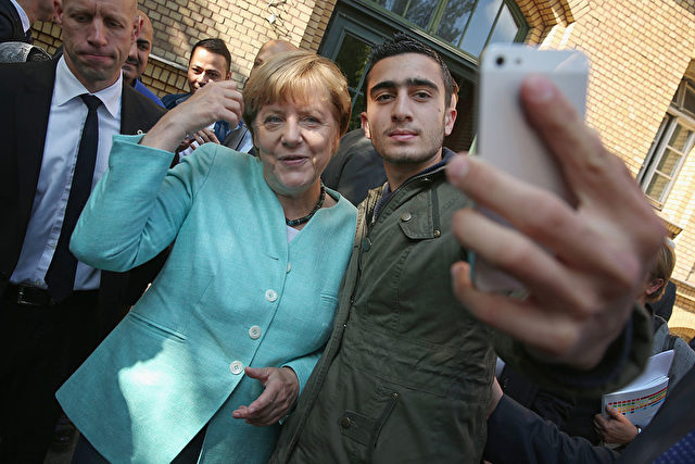 Kanzlerin Merkel und ein Flüchtling machen ein Selfie Foto:  Sean Gallup/Getty Images