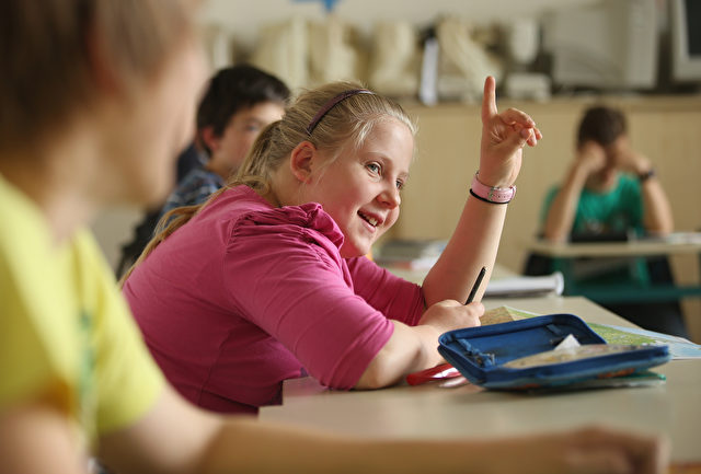 """SEIFHENNERSDORF, GERMANY - MAY 14:  Sixth grader Linda Weitz, 12, raises her hand during geography class at the Middle School on May 14, 2014 in Seifhennersdorf, Germany. The state of Saxony officially closed the Seifhennersdorf Middle School in 2012 after only 38 students registered, two short of the 40 the state required to keep the school open. Rather than agree to the school's closing, a group of parents and other volunteers have since assumed the duties of teachers and staff themselves and are trying to get recognition of their """"illegal"""" school through a court case that now lies with Germany's Federal Constitutional Court. Eleven 6th graders attend the school, even though the state does not recognize their enrollment. School closings across Germany have reached epidemic proportions with 6,100 closures between 2003 and 2013, due in large part to Germany's low birth rate, a phenomenon typical across much of Europe. In Saxony the low birth rate has combined with a steady migration of young people to big cities and to western Germany and the number of schoolchildren has fallen by close to 50% and led to the closure of 1,000 out of a total of 2,500 state schools since 1989.  (Photo by Sean Gallup/Getty Images)"""