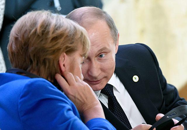 Der russische Präsident  Wladimir Putin (R) und Kanzlerin Angela Merkel Foto: ALAIN JOCARD/AFP/Getty Images