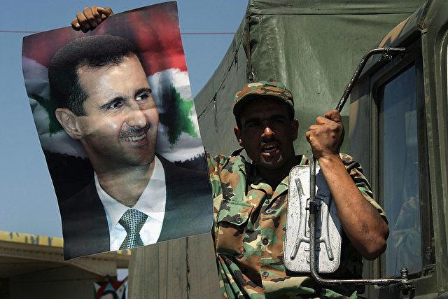 Ein syrischer Soldat hält das Bild von Präsident Baschar al-Assad. Foto: Ghaith Abdul-Ahad/Getty Images