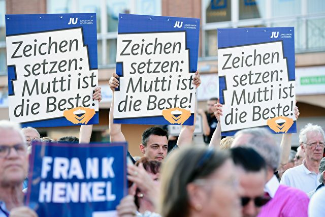 Supporters of German Chancellor Angela Merkel and Christian Democtaric Union (CDU) candidate Frank Henkel hold up placards as they wait for her to arrive for an electoral meeting of the Christian Democtaric Union (CDU) party ahead of the weekend's state elections in Berlin of September 14, 2016. / AFP / TOBIAS SCHWARZ (Photo credit should read TOBIAS SCHWARZ/AFP/Getty Images)