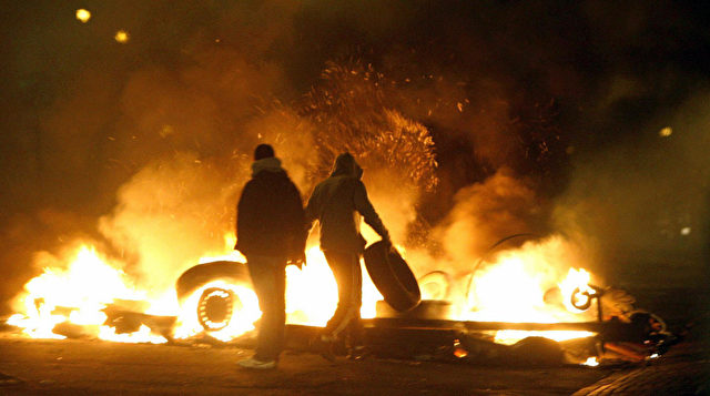 People stand in front of burning barricades on the main road of the Rosengard suburb of Malmo, southern Sweden, on December 18, 2008. Some 100 youths rioted in the southern Swedish town of Malmoe late Thursday for the second straight night, setting cars and garbage bins ablaze and throwing stones at police, police said. Police spokeswoman Ewa-Gun Westford said the troubles were linked to the recent closure of an Islamic cultural centre in Malmoe's heavily-immigrant populated neighbourhood Rosengaard. AFP Photo / Drago Prvulovic / SCANPIX ** SWEDEN OUT ** (Photo credit should read DRAGO PRVULOVIC/AFP/Getty Images)