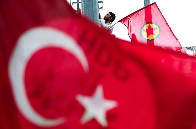 Auf einer Pro-Kurden-Demonstration in der Türkei, hält ein Mann eine Flagge der PKK (Kurdischen Arbeiter Partei) hinter einer türkischen Flagge und einer Flagge der Pro-kurdischen Partei HDP.   Foto: OZAN KOSE/Getty Images