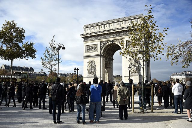 People observe a minute of silence at the top of the Champs-Elysees avenue by Arc de Triomphe monument in Paris on November 16, 2015 to pay tribute to victims of the attacks claimed by Islamic State which killed at least 129 people and left more than 350 injured on November 13.  AFP PHOTO / FRANCK FIFE        (Photo credit should read FRANCK FIFE/AFP/Getty Images)