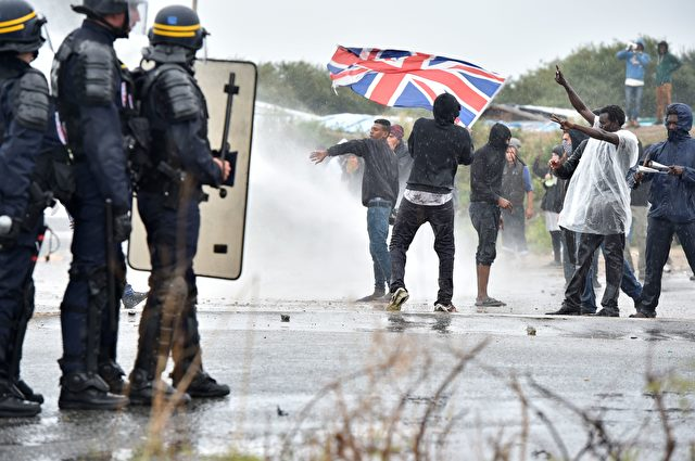 "A participant holds up the Union Jack as French anti-riot police fire water canons at participants during a march in support of migrants and refugees in the so-called 'Jungle' camp in the French northern port city of Calais on October 1, 2016. Between 7,000 and 10,000 migrants are currently living in the ""Jungle"", the launchpad for their attempts to stow away on lorries heading across the Channel to England. Rights groups have criticised the hardship and dangers facing the migrants living in the camp, particularly the hundreds of unaccompanied minors. / AFP / PHILIPPE HUGUEN (Photo credit should read PHILIPPE HUGUEN/AFP/Getty Images)"