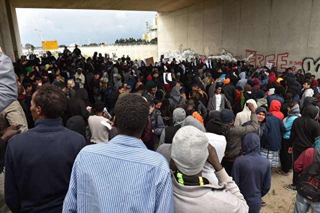 "Participants gather during a march in support of migrants and refugees in the so-called 'Jungle' camp in the French northern port city of Calais on October 1, 2016. Between 7,000 and 10,000 migrants are currently living in the ""Jungle"", the launchpad for their attempts to stow away on lorries heading across the Channel to England. Rights groups have criticised the hardship and dangers facing the migrants living in the camp, particularly the hundreds of unaccompanied minors. / AFP / PHILIPPE HUGUEN (Photo credit should read PHILIPPE HUGUEN/AFP/Getty Images)"