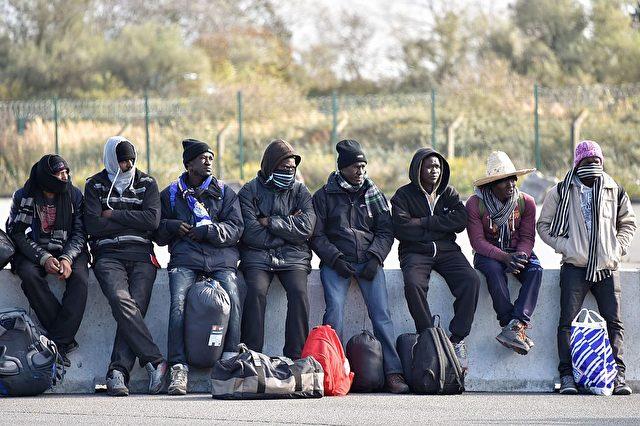"""Junge Migranten warten auf den Bus, weg vom geräumten """"Dschungel"""" Calais. Sie werden in Aufnahmezentren in ganz Frankreich verteilt. Auch nach Deutschland könnten laut Dublin-Abkommen Hunderte von ihnen kommen. Foto: PHILIPPE HUGUEN/AFP/Getty Images"""