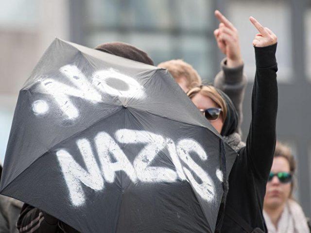 Gegendemonstranten protestieren in Dortmund gegen eine Demo von Hooligans und Neonazis. Foto: Marius Becker, dpa/dpa
