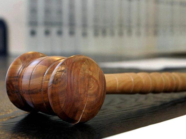 Ein hölzerner Hammer auf der Richterbank eines Verhandlungssaals. Foto: Uli Deck/Symbolbild/dpa