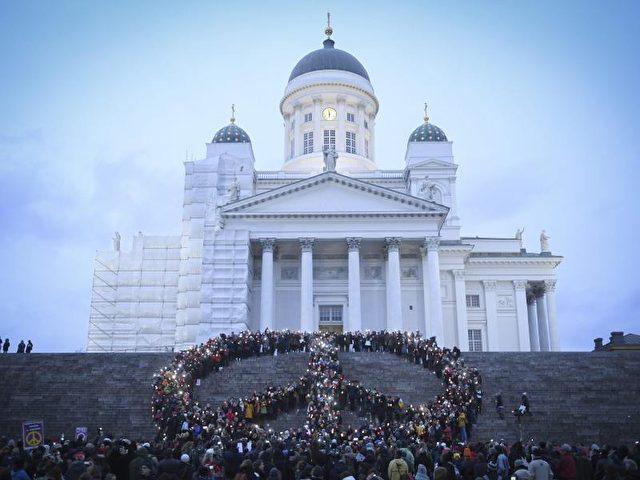 Vor dem Dom von Helsinki bilden Menschen ein großes Friedenszeichen. Foto: Kimmo Brandt/dpa