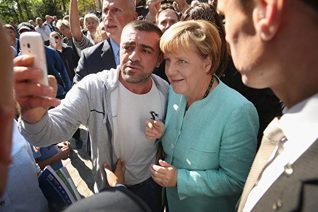 Kanzlerin Merkel macht Selfies mit Flüchtlingen. Foto: Sean Gallup/Getty Images