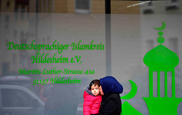 """HILDESHEIM, GERMANY - NOVEMBER 08: A woman of the muslim community walks by a mosque where hours earlier they arrested Ahmad Abdulaziz Abdullah A., alias """"Abu Walaa"""", a 32-year-old imam from Iraq, on November 8, 2016 in Hildesheim, Germany. Police announced they arrested five men today in Lower Saxony and North Rhine-Westphalia on charges of recruiting fighters for the Islamic State (IS). (Photo by Alexander Koerner/Getty Images)"""