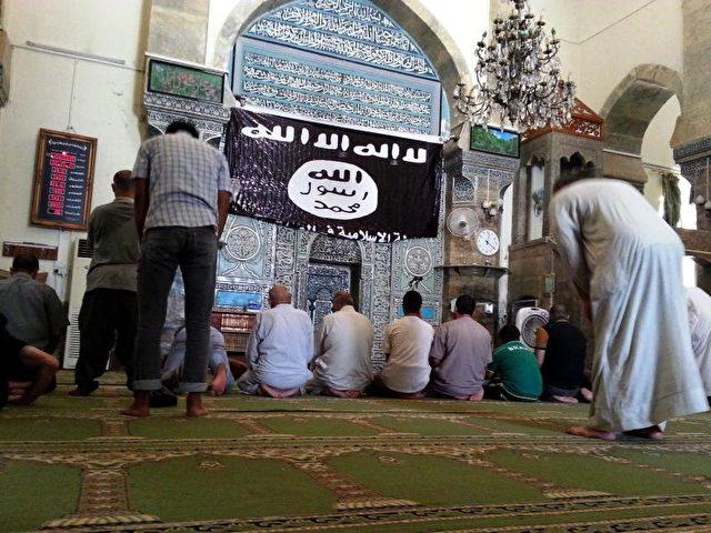 Gläubige beten unter einer IS-Flagge in Mossul, Irak. Foto: dpa/dpa