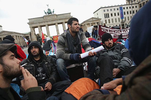 BERLIN, GERMANY - OCTOBER 17:  Refugees from Iraq, Iran and Afghanistan keep warm on the 8th day of a hunger strike in front of the Brandenburg Gate on October 17, 2013 in Berlin, Germany. 28 refugees, some of whom have been in Germany for as long as seven years waiting for their asylum applications to be processed, are participating and many have refused to drink any liquids since October 11, and say they will do so until the German government makes a firm commitment to helping them. About a dozen of the refugees have already been hospitalized, and most have come back to participate further in the hunger strike.  (Photo by Sean Gallup/Getty Images)