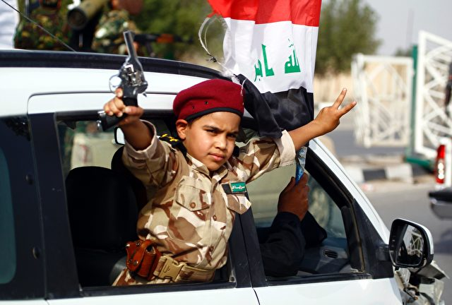 A young supporter of the Saraya al-Salam (Peace Brigades), a group formed by Iraqi Shiite Muslim cleric Moqtada al-Sadr, holds a weapon and flashes the sign for victory in Iraq's holy city of Najaf as the pro-government paramilitary group prepare to reinforce government forces in the fight against the Islamic State group for control of Fallujah, east of the capital, on May 17, 2016.     Iraqi security forces and allied fighters have regained significant ground from the jihadists, securing the Ramadi area earlier this year and retaking the town of Heet last month. But parts of Anbar -- including Fallujah -- are still under IS control, as is most of Nineveh province, to its north.   / AFP / HAIDAR HAMDANI        (Photo credit should read HAIDAR HAMDANI/AFP/Getty Images)