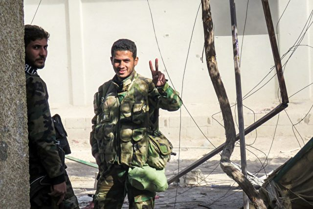 A Syrian Army soldier flashes the sign of victory during Syrian forces' assault to capture the rebel-held village of Hawsh Nasri, which is located near the rebel-held town of Douma on the eastern outskirts of the capital Damascus. / AFP / STRINGER        (Photo credit should read STRINGER/AFP/Getty Images)