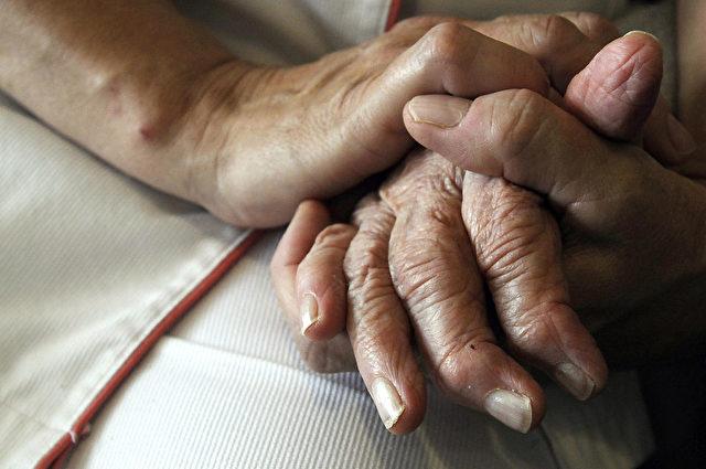 Krankenschwester hält die Hand einer Alzheimer-Patientin Foto: SEBASTIEN BOZON/AFP/Getty Images)