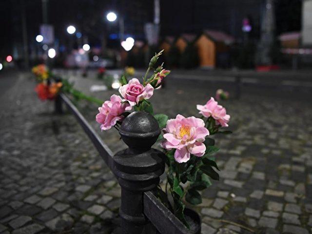 Blumen zum Gedenken an die Opfer stecken an einem Geländer vor der Gedächtniskirche in Berlin. Foto: Britta Pedersen/dpa