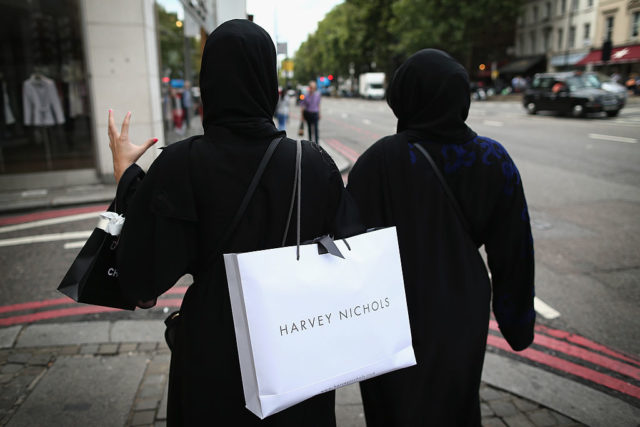 LONDON, ENGLAND - AUGUST 06:  Two muslim women wearing black Abayas and head scarfs walk through Knightsbridge holding fashionable shopping bags on August 6, 2014 in London, England. Tourists and car enthusiasts have been flocking to the wealthy London district to see some of the world's most expensive and extravagant super cars. Many of the rich owners from Saudi Arabia and Kuwait come to London to escape the summer heat at home and to show off their cars before moving on to other European cities such as Paris and Cannes.  (Photo by Dan Kitwood/Getty Images)