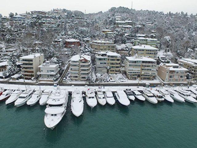 Eine Luftaufnahme zeigt schneebedeckte Boote auf dem Bosporus in Istanbul. Foto: Ali Aksoyer/dpa