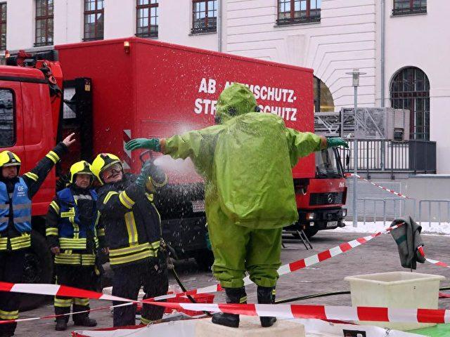 Feuerwehrleute in Schutzanzügen stehen im Justizzentrum in Gera, wo ein Brief mit weißem Pulver gefunden wurde. Foto: Bodo Schackow/dpa