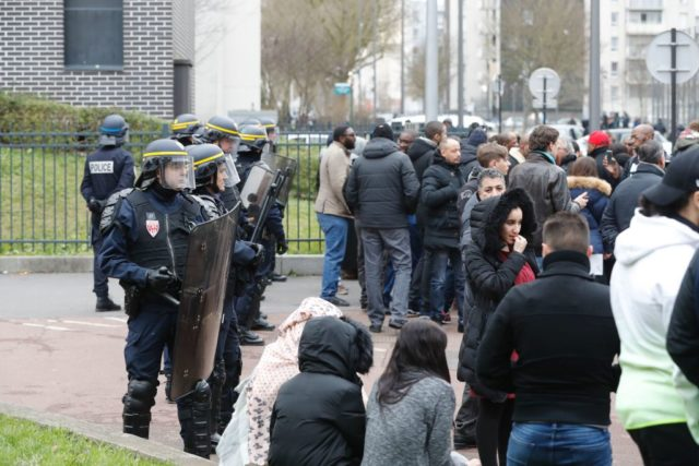 """French anti riot police officers (L) stand guard as people gather during a protest on February 6, 2017 in Aulnay-sous-Bois, northern Paris, a day after a French police officer was charged with the rape of a youth who was severely injured after allegedly being sodomised with a baton. Hundreds of people were marching on February 6, 2017 in Aulnay-sous-Bois to demand justice for the alleged victim, described by family and friends as a youth worker who came from a respected family in the area. Interior Minister Bruno Le Roux confirmed late February 5 that all four officers had been suspended during the investigation, adding that exemplary conduct and respect """"must guide the behaviour of security forces at all times"""". / AFP / FRANCOIS GUILLOT        (Photo credit should read FRANCOIS GUILLOT/AFP/Getty Images)"""