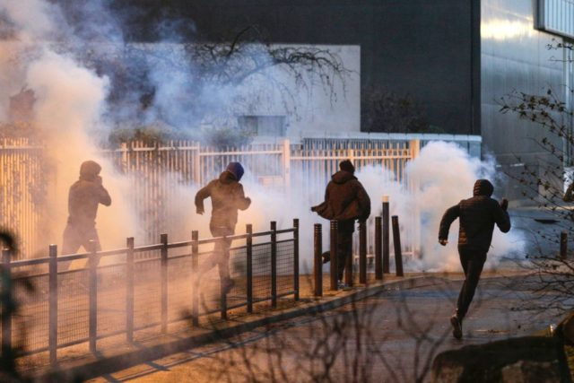 "People run as anti riot police spread tear gas in Bobigny, northern Paris, on February 16, 2017 during a demonstration to demand justice for Theo, a 22-year-old youth worker who required surgery after his arrest last week in the gritty suburb of Aulnay-sous-Bois. French President Francois Hollande called for ""justice"" over the alleged rape of a black youth with a police baton, an incident that has sparked 10 nights of rioting and more than 200 arrests. / AFP / GEOFFROY VAN DER HASSELT        (Photo credit should read GEOFFROY VAN DER HASSELT/AFP/Getty Images)"