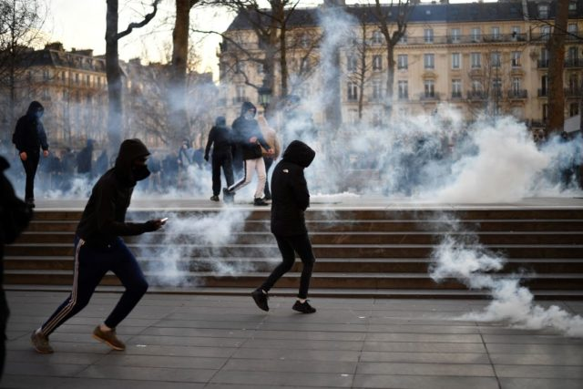 Protestors run amid teargas during a demonstration against police brutality on February 18, 2017 on the place de la Republique in Paris, following the alleged rape of a black youth, identified only as Theo, with a police baton, an incident that has sparked 10 nights of rioting and more than 200 arrests.The injuries sustained by Theo during a stop-and-search operation on February 2 in the suburb of Aulnay-sous-Bois, has revived long-simmering frustrations over policing in immigrant communities, where young men accuse the police of repeatedly targeting them in aggressive stop-and-search operations and using excessive force during arrests.  / AFP / Lionel BONAVENTURE        (Photo credit should read LIONEL BONAVENTURE/AFP/Getty Images)