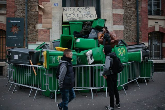 "Students stand on a barricade made with dustbins as they protest against police brutality, following the alleged rape of Theo, outside the ""Lycee Dorian"" secondary school in Paris, on February 23, 2017. / AFP / GEOFFROY VAN DER HASSELT (Photo credit should read GEOFFROY VAN DER HASSELT/AFP/Getty Images)"