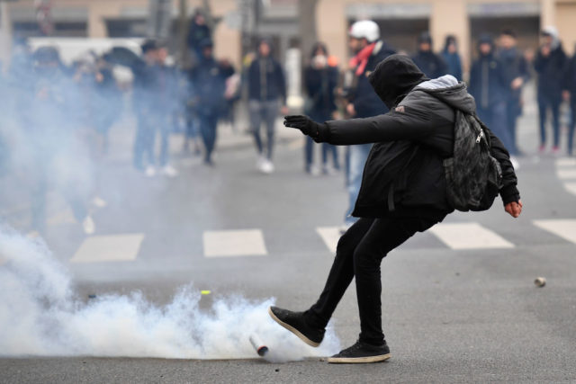 "A man kicks away a smoke grenade launched by riot police during a protest of students against police brutality, following the alleged rape of Theo, next to the ""Lycee Voltaire"" secondary school in Paris, on February 23, 2017. / AFP / Lionel BONAVENTURE (Photo credit should read LIONEL BONAVENTURE/AFP/Getty Images)"
