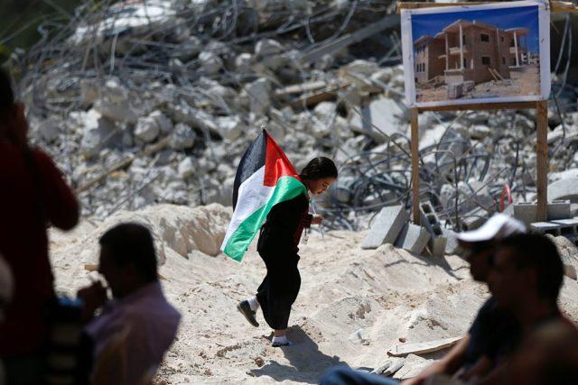 Ein Kind mit einer Palästinaflagge im von Israel zerstörten Palästinenserdorf Qalandia. 29. Juli 2016. Foto: ABBAS MOMANI/AFP/Getty Images