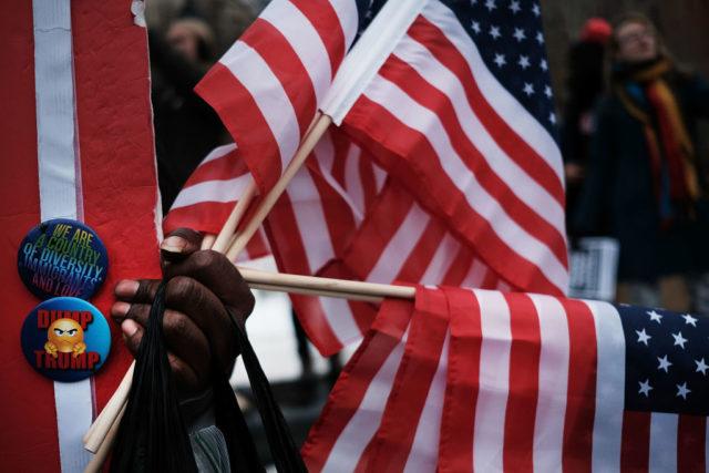 Ein Mann verkauft Sticker und US-Flaggen auf einer Anti-Trump-Dem Foto: Spencer Platt/Getty Images