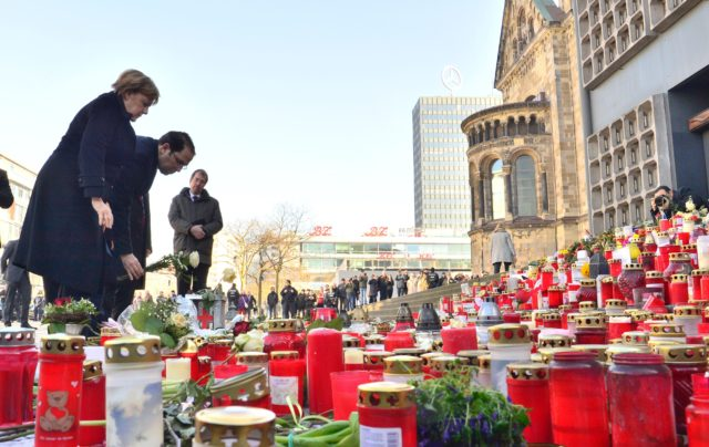 German Chancellor Angela Merkel (L) and Tunisian Prime Minister Youssef Chahed (2nd L) lay down flowers at the site where happened the Berlin Christmas Market attack, on February 14, 2017 at Breitscheidplatz near the Kaiser-Wilhelm-Gedaechtniskirche (Kaiser Wilhelm Memorial Church) in Berlin. On December 19, 2016, suspected jihadist attacker Tunisian Anis Amri ploughed a hijacked truck into a Berlin Christmas market, killing 12 people, including the vehicle's registered driver.  / AFP / John MACDOUGALL        (Photo credit should read JOHN MACDOUGALL/AFP/Getty Images)