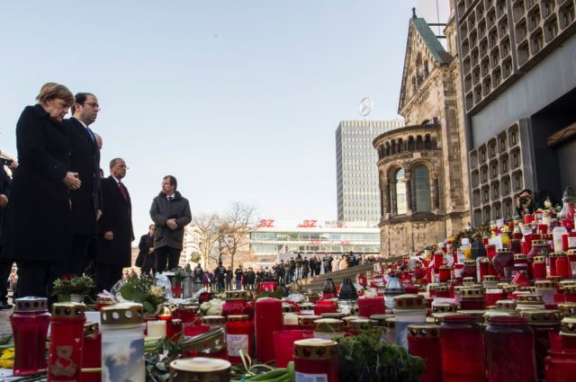 German Chancellor Angela Merkel (L) and Tunisian Prime Minister Youssef Chahed (2nd L) lay down flowers at the site of the Berlin Christmas Market attack, on February 14, 2017 at Breitscheidplatz near the Kaiser-Wilhelm-Gedaechtniskirche (Kaiser Wilhelm Memorial Church) in Berlin. On December 19, 2016, suspected jihadist attacker Tunisian Anis Amri ploughed a hijacked truck into a Berlin Christmas market, killing 12 people, including the vehicle's registered driver. / AFP / John MACDOUGALL (Photo credit should read JOHN MACDOUGALL/AFP/Getty Images)