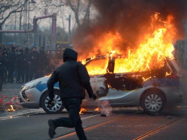 Vermummte Demonstranten haben 2015 vor der Eröffnung der neuenEZB-Zentrale in Frankfurt einen Polizeiwagen angezündet. Angriffe auf Einsatzkräfte sollen künftig strenger bestraft werden. Foto: Arne Dedert/dpa
